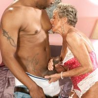 Busty stocking and lingerie clad 70 plus granny Sandra Ann giving big black cock a blowjob