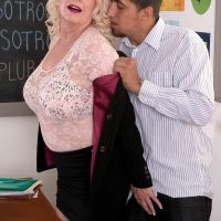 Buxom blonde 60 plus MILF teacher Angelique DuBois jerking big cock in classroom
