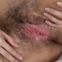 Leggy brunette amateur Tracy Rose oiling hairy pussy for spreading of labia lips