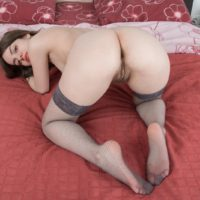 Brunette amateur stripping off stockings while baring hairy armpits and beaver