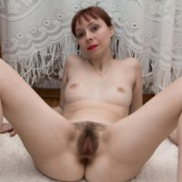 European solo girl with small breasts sliding underwear aside to expose hairy pussy