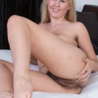 Lingerie attired blonde amateur Aali Rousseau sliding panties aside to expose beaver