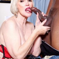 Nylon and lingerie attired granny Lola Lee giving huge black cock BJ with big tits out
