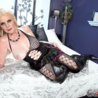 Over 60 blonde MILF unveiling large natural tits in ripped stockings and long boots