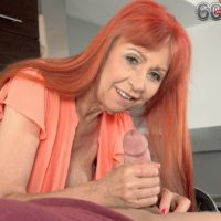 Redheaded granny with great legs and big natural tits giving handjob in kitchen