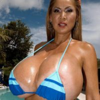 Top heavy Asian solo girl Minka oiling huge bikini clad juggs outdoors by pool