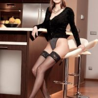 Brunette babe Estelle Taylor flaunting large natural tits in black stockings and heels