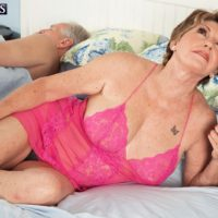 Busty redhead granny Bea Cummins jerking off big dick while cuckold husband sleeps