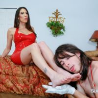Clothed brunette Domme Dava Foxx instructing crossdressing sissy maid with crop