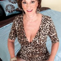 Solo granny Sydni Lane teasing on bed by flashing brassiere in pantyhose