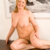 Clothed mature woman revealing large boobs before spreading hairy vagina in office