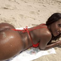 Black solo girl Sapphira showing off big booty on beach wearing red swimsuit