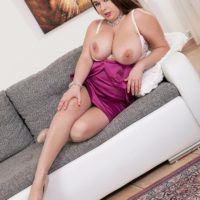 Brunette MILF Monica Love letting huge boobs loose from bra and dress in heels