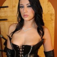 Dark haired Domme Ashley strutting about dungeon partly naked in fetish garb