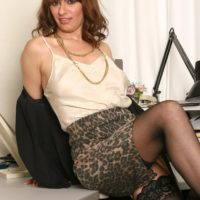 Naughty older boss lady stripping down to stockings and high heels in her office