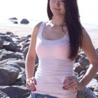 Petite brunette amateur Olivia showing off perky teen tits outdoors on rocky beach