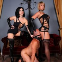 Sexy Dommes Belle Noir and Brianna abuse collared male slave in fetish clothing