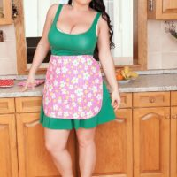 Brunette solo girl Juliana Simms letting huge tits loose from dress in kitchen
