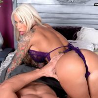Tattooed blonde MILF pornstar Lolly Ink revealing round boobs for nipple sucking