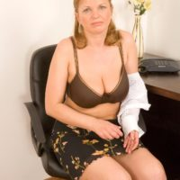 Middle aged woman taking off skirt and lingerie to model naked at office desk