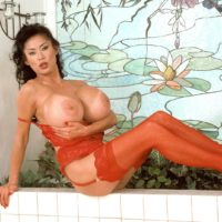 Top Asian pornstar Minka releasing her huge tits from bra wearing red stockings