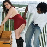 Chubby brunette Daphne Rosen shows off her big ass in black boots on blacony