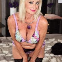 Blonde granny Leah L'Amour gives her boy toy a handjob in lingerie and stockings