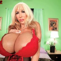 Blonde solo model Elizabeth Starr showcases her monster tits in a red bra