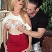Older blonde lady Charlie has her big boobs exposed by younger man in a red skirt