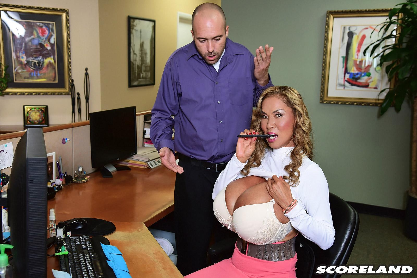 Asian woman Minka seduces a coworker with her massive tits at work