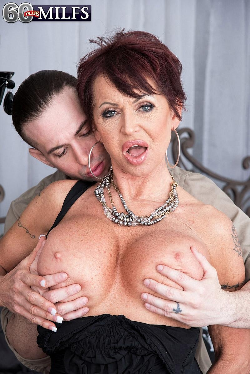 Classy mature woman Gina Milano seduces a younger man with her huge boobs