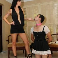 Dark haired wife Angie Noir face fucks her sissy with a big strapon cock in high heels