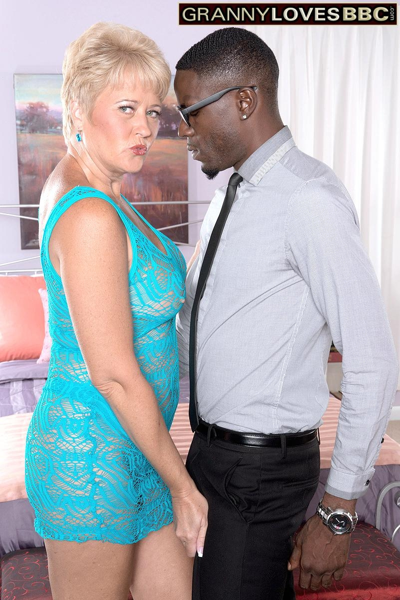 Horny granny Tracy Licks flashes her bare tits to a black man in a revealing dress