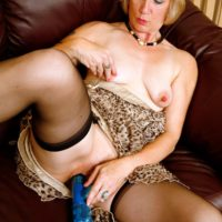 Mature blonde lady hikes up her dress in order to toy her pussy in black stockings