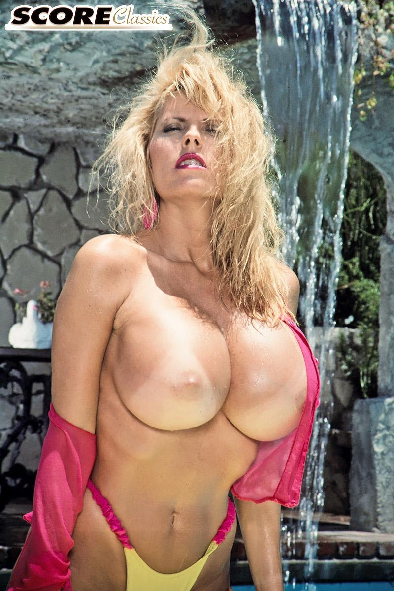 Older pornstar Kimberly Kupps releases her large boobs from bikini top by the pool