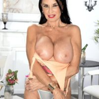 Top mature pornstar Rita Daniels uncovers her huge boobs and flashes her panties too