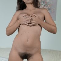 Brunette amateur Camille S showing off small tits before spreading hairy pussy