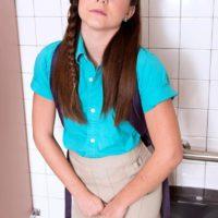 Brunette schoolgirl Kharlie Stone sliding panties over ass before pissing