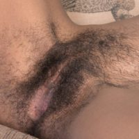 Ebony amateur with tiny saggy boobs revealing hairy black pussy on couch