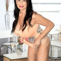 Over 60 brunette MILF Rita Daniels showing off great legs and huge knockers