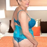 Short haired 60 plus MILF Lin Boyde freeing large tits from lingerie in stockings