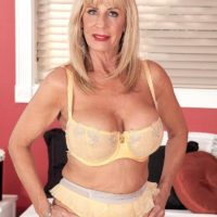Stocking and lingerie clad mature pornstar Phoenix Skye baring big tits and giving massage