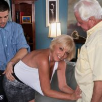 Blonde granny Scarlet Andrews exposing large boobs before cuckold husband