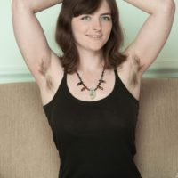 Brunette amateur sheds dress and panties to reveal hairy underarms and beaver