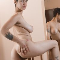 Busty and tattooed European amateur Sue displaying hairy underarms and pussy