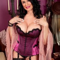 Lingerie and stockings attired mature pornstar Rita Daniels licking big cock with tongue