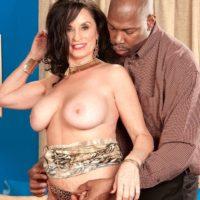 Mature brunette pornstar Rita Daniels exposing big tits before interracial sex