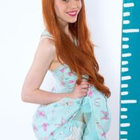 Redheaded teen pornstar Dolly Little exposing small breasts in cute panties