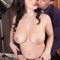 Stocking clad dark haired pornstar Noelle Easton freeing nice melons from lingerie