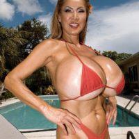 Top heavy Asian solo girl Minka oiling huge bikini clad juggs outdoors by pool